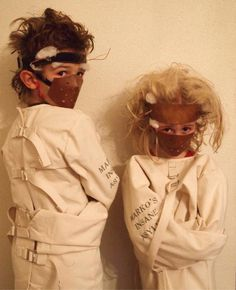 Two children dressed up in straight jackets with ect headbands and mouth guards.