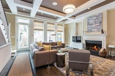 The chocolate brown ceiling is accented with white beams perfectly complimenting the neutral color palette in the room. Yellow in the patterned rug is echoed with yellow throw pillows adding color to the beige sectional. Natural light from the windows brighten the small space keeping it comfortable and inviting.