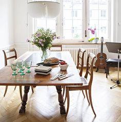 Ruokailuhuoneessa on vanha leveä kalanruotoparketti, jykevä ruokapöytä ja biedermeier-tuolit. Pöydällä Iittalan Verna-lasit ja Zeenatin keramiikka-astioita | Onnellisesti vuokralla | Koti ja keittiö | Jutta Ylä-Mononen  | Kuva Kirsi-Marja Savola