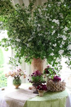 large centerpiece of branches of dogwood, spiraea, mock orange, smaller arrangements at base in unique containers, by Ariella Chezar