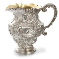 A Fabergé Silver Cream Pitcher, Moscow, circa 1910, in the neo-Rococo taste, with bunches of flowers set against scrolls and swags in low relief, with an ornate, scrolling handle, the interior gilded.