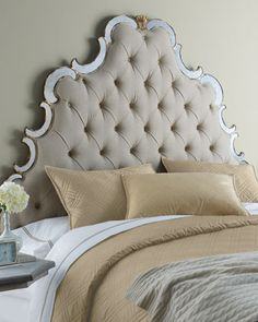 Regal, tufted headboard in medium taupe is edged with swirls of antiqued mirror and wooden accents with hand-painted golden highlights.