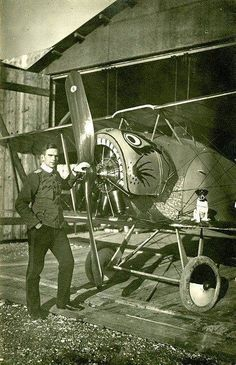 A German pilot stands next to a Fokker DII while a dog poses on the wing, ca. 1916.