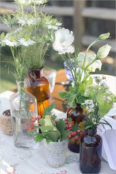 mixing and matching vintage bottles, centerpieces with vintage brown bottles www.flowersbydenise.com