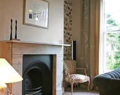 quirky reception area with vintage chesterfield sofas, feature wallpaper and carrara marble fireplace