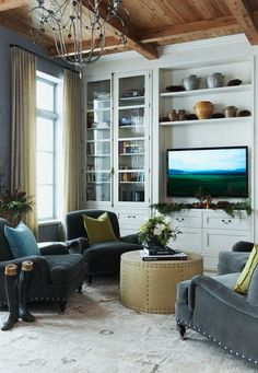 This living room has a nice combination of colors, with soft gray chairs and lime green accents. The TV makes a nice focal point, and the cabinet provides shelving for Blu-rays, DVDs, and other knick-knacks.