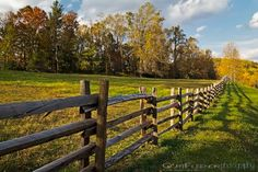 Sunset begins to cast a warm glow across a field bordered by autumn colors and a split rail fence.