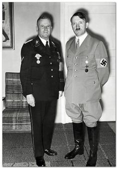 One of Hitler's best uniforms (thank God for no belt). He's standing with Ulrich Graf, who had been a Nazi party member from its very earliest days. Love the art deco chair in the background. (via putschgirl)