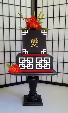Birthday cake for my son (26 today).   Chocolate with fresh raspberry filling and dark chocolate ganache. Gum paste orchids, bamboo and buds. I used the paneling technique for the first time with the black fondant. The white squares are made from fondant strips with 45 degree angle cuts. Stenciled Asain Characters and painted in gold. The character you cand see means Love.  Much more labor intensive than I anticipated but I am pleased. Cake stand  by BatterUpCakes.