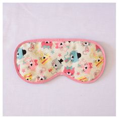 """Máscara de Dormir """"Gatinhos"""" Para que o seu sono seja relaxante a qualquer momento!   Descrição:   Tecido 100% algodão (estampa)  Enchimento de manta acrílica  Acabamento com viés (rosa)  elástico chato regulável (preto)  Fundo preto (tecido de algodão)   Medidas:   20 cm (comprimento)  10 cm (largura)  10g. #máscaradedormir #máscaraparadormir #máscarasdedormir #máscarasparadormir #tapaolho #tapasolhos #evitaclaridade #acessório #acessórios #acessóriodeviagem"""