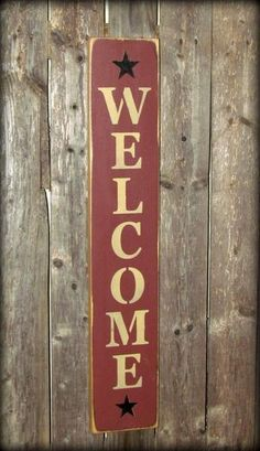 """This wooden welcome sign is made from pine, and measures Approximately 4.5""""W x 25""""L. It reads """"Welcome"""". The front is painted barn red then distressed, the back"""