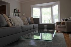 living room bay windows, glass waterfall table, grey couch, neutral family room