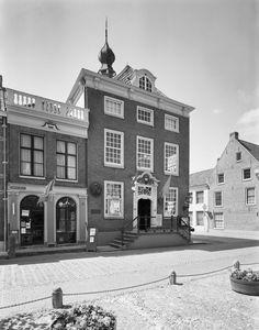 Markt 1 Raadhuis  Stadhuis. In oorsprong 16e eeuws woonhuis aan de Markt op de hoek van de Peperstraat en de Rode Heldenstraat, aangekocht door de stad in 1554 en omstreeks 1610 in renaissancetrant verbouwd, waarna het in 1739-'40 werd gemoderniseerd en een nieuwe voorgevel met bordes, waarop een smeedijzeren hek, een gesneden deuromlijsting in Lodewijk XIV vormen en een kroonlijst met verdiepte panelen met consoles verkreeg. Op het nog 17e eeuwse dak een sierlijk houten torentje met peer...