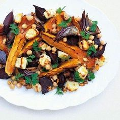 Roasted Butternut Squash and Halloumi Salad Recipe Ideas - Healthy & Easy Recipes 1 medium butternut squash 4 small uncooked beetroot 2 small red onions, quartered 3 large cloves garlic, peeled Olive oil 150g (5oz) halloumi, cut into 2cm (3/4in) cubes 400g (14oz) tin chickpeas, drained Ground coriander seeds 1tsp sumac Parsley leaves, to serve Extra virgin olive oil, to serve METHOD Heat the oven to 200°C (gas mark 6). Cut the butternut squash into eight wedges lengthways. Remove the reserve