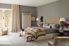 Design-savvy stars Ellen DeGeneres and Portia de Rossi created a lively, art-filled home in Beverly Hills. The master bedroom is a chic and calming refuge, with walls upholstered in a warm gray flannel by Holland & Sherry. (November 2011)