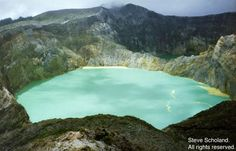 "A volcanic lake - Indonesia  Tiwo Nua Muri Koohi Fah  - The lake of ""young men and maidens""  (The yellow is sulpher released by the magma through the volcanic pipe."