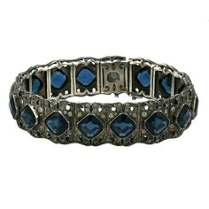 Art Deco paste bracelet with square faux sapphires with pastes. Tiny marquises shaped sapphire stones edge the sides of each square stone. 1930s France. 7 x 5/8 wide.