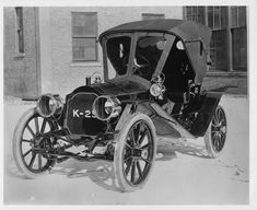 """1908 Packard 30 Model UA, """"K-25"""" painted on radiator grill. Inscribed on photo back: 4-cylinder, 30-horsepower, 108-inch wheelbase, 2-person runabout, with cowl swept back along body sides, folding leather victoria top having roll-up front, tube radiator, 1908 type radiator cap, monogram on side of seat, apparent absence of rumble seat, patent leather aprons fitted between fenders and frame."""
