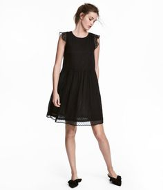 Black. Knee-length dress in soft woven fabric. Opening at back of neck with button. Short, ruffled sleeves, seam at waist, and flared skirt. Lined.