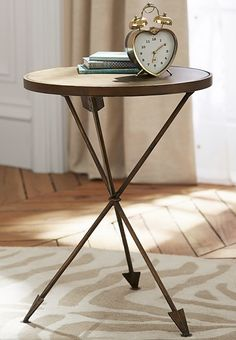 This imaginative table combines classic elements with creative design. The round top stands upon three arrow-shaped legs, and an antique brass finish provides a hint of shine to transform a staple piece into a favorite.