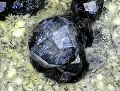 Analcime,Natrolite Colorless 1mm trapezohredon of analcime with white needles of natrolite.