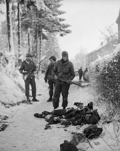 US soldiers search a dead German. Battle of the Bulge.