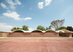 Curving vaults give Mesura's red brick extension to IV House in Spain's Alicante province a scalloped roofline