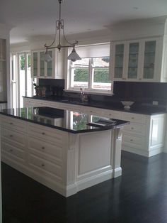 Indah island white cabinets with black granite benchtops More