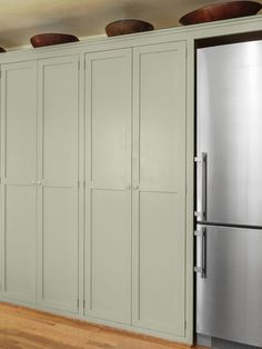 pantry cabinets in wall along fridge, retro style kitchen with soft green cabinets and salvage apron sink