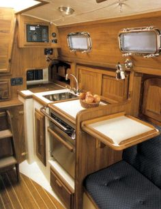 """Dana 24 galley: A cover over the stove provides added workspace, as does the optional flip-up counter top to its right. The sink is 10"""" deep. There's a 2-burner stove, galley lockers and a large ice box. [Image from the original Pacific Seacraft brochure]"""