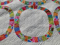 This quilt pattern is called Single Sisters, and the quilting desgin is called Daisy Square. I picked this small design would give it fun detail and still draw your eye to the pattern. I love the squarishness of the Dasies complimenting the squarishness of the cirlces! This fun summer quilt was one of the largest quilts we've made! We use longarm quliting machines to stitch the design you want to the pattern you adore!