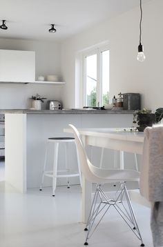 Kitchen, white cabinets, concrete countertop, white diningtable and chairs, single shelf