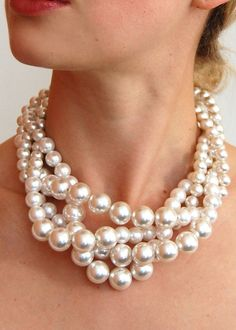 "Classic pearl necklace of various sized pearls, twisted to perfection. Makes a great statement! Sits high on neck, choker style. Measures 20"" around the neck at it's longest point."