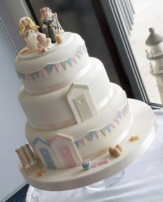 Beach themed three tier wedding cake with pastel colours, beach huts and deckchairs. Cute model of the happy couple and their daughter too.