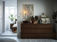 Dos cómodas marrones con mucho espacio para guardar prendas de vestir y ropa de cama, y para poner libros y plantas encima.