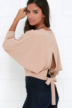 When in doubt about what to wear, the Branch and Vine Beige Crop Top is sure to save the day! Soft woven fabric begins at a rounded neckline before draping into long dolman sleeves. Overlapping back fastens uniquely with two buttons at the neckline, while two wide straps tie below.