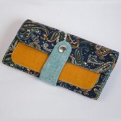 Яркий женский кошелек – клатч Handmade от молодого украинского бренда Yak Faino из трех видов ткани – джинс, лен и хлопок с основным узором – арабесками. Кошелек состоит из следующих отделений – трех для бумажных купюр и мобильного телефона, шести для карточек, двух отд