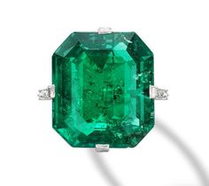 An emerald and diamond ring, by Van Cleef & Arpels, 1920. The 18.67 carat octagonal step-cut emerald within a delicate mount millegrain-set with single-cut diamonds and engraved decoration.