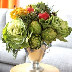 Not all floral arrangements need to have flowers. This arrangement showcases the bounty of fall in all its glory, with cabbages, artichokes, pomegranates and other seasonal fruits and vegetables. includes easy step by step instructions with pics Fruit Centerpieces, Edible Arrangements, Winter Vegetables, Fruits And Vegetables, Seasonal Fruits, In Season Produce, Fruit In Season, Vegetable Bouquet, Fruit Flowers