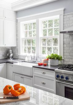 Beautiful kitchen with double sash windows over the farmhouse sink paired with a bridge gooseneck faucet framed by soapstone counters which pair with a beveled subway tile backsplash alongside white cabinetry adorned with polished nickel cabinet pulls with white and gray quartzite topped kitchen island in the foreground.