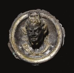 Hellenistic silver-gilt roundel with bust of the God Pan, 3rd-2nd Century B.C. Possibly an emblem from a dish or a fulcrum, cast in high relief with the young goat-horned deity turned to his right and wearing a chlamys, his grinning face with delineated upper teeth, high arched eyebrows, and furrowed forehead, the hair and ear markings carefully chased, 6 cm diamater. Private collection