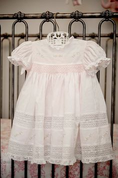 The dress is pale pink swiss batiste with a lot of delicate Custom Keepsakes machine embroidery, embroidery, lace, smocking and a beautiful baby. What could be sweeter?
