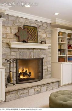 FIREPLACES: Stone fireplace with suspended mantel, game boards, crown molding, bookshelves with crocks, and boxes, ottoman
