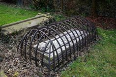 1. Victorian grave from when they feared zombies and vampires. The cage was put over the grave to trap the potential zombie inside in case the deceased came back as the undead.    2. A mortsafe. A device invented to deter grave robbers that were paid by anatomists, who had no legal way to procure cadavers, to find corpses for them to dissect.     ~ I like the zombie story better.