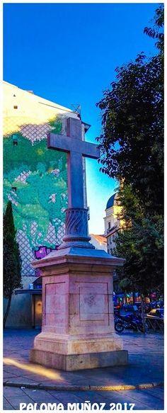 Dos de las señas de identidad de la Plaza de Puerta Cerrada: la cruz de piedra de 1738, el trampantojo de una enredadera en una fachada, mural pintado por Alberto Corazón en 1983. A la derecha, asoma la cúpula de la Colegiata de San Isidro. Two of the signs of identity of the urban area of Puerta Cerrada: the stone cross of 1738 and behind it, the trompe l'oeil of a vine in a façade, mural painted by Alberto Corazón in 1983. To the right, the dome of the Collegiate Church of San Isidro…