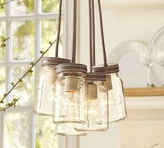 pottery barn 5 jar chandelier glass canning jars suspended from a galvanized canopy on gray fabric cords of different lengths. How To Make Light, Decor, Jar Pendant Light, Mason Jar Chandelier, Jar Chandelier, Glass Canning Jars, Mason Jar Light Fixture, Mason Jar Lamp, Mason Jars