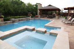 Clean lines on this square shaped spa blend nicely with the classic design of the swimming pool. By Outdoor Signature in Argyle, TX