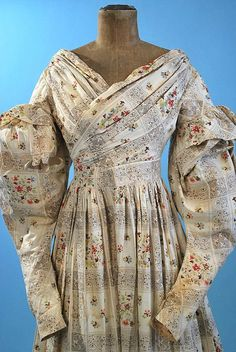 """Roller print cotton dress, all original, dating to late 1820's, early 1830s. Dropped, piped and ruffled capped gigot sleeves, criss cross draped front bodice with slightly to the back piped shoulder seams, cartridge pleating around waist, wide waist band, back hook & eye closure. Bodice only lined in linen with pocket hanging from bottom of bodice interior. Hem faced in household cotton. All hand stitched. Bust: 32""""; waist: 22""""; sleeves: 26"""", length from shoulders: 53""""."""