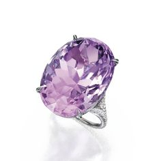 18 Karat White Gold, Kunzite and Diamond Ring Set with an oval-shaped kunzite weighing approximately 56.75 carats, the mounting accented by numerous round diamonds weighing approximately .45 carat