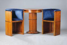 Tischgruppe, deutsch, um 1906, bestehend aus: Tisch und zwei Sesselstühle, Entwurf A. Reimann, Berlin, sog. Schalenstühle, Nussbaum massiv, senkrecht gerieft, auf Nute verarbeitet, Mittelteil mit ovalen schwarzen Appliken unterbrochen, reiner abstrakter Jugendstil von hoher Qualität, sammelwürdig, museal, Unikatcharakter, Altersspuren, Sesselstühle ca. 83x54x46cm, Sitzhöhe ca.52cm,Tischsäule mit zu öffnender Tür, typisch als Salonmöbel konzipiert für Ablage der Visitenkarten, ca. 83x69cm